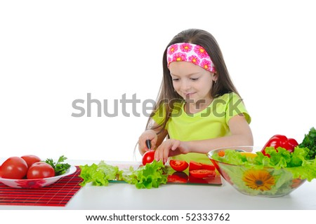 little girl is preparing salad at the table. Isolated on white background - stock photo