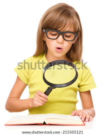 Little girl is reading book using magnifier while sitting at table, isolated over white - stock photo