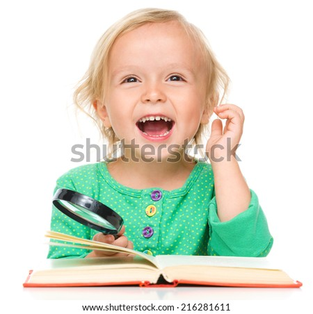 Little girl is reading her book using magnifier, isolated over white - stock photo