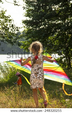 Little girl is running with kite at sunny day - stock photo