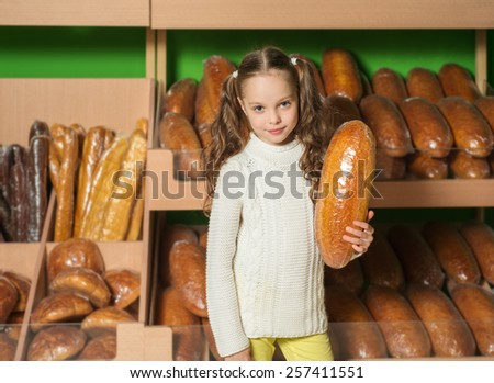 Little girl is shopping in supermaket, bakery, bread - stock photo