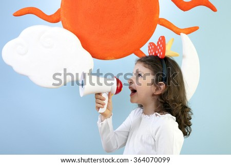 Little girl is shouting and protesting over megaphone against blue background. - stock photo