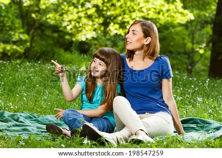 Little girl is showing something to her mother while they sitting and enjoy in nature,Mother and daughter enjoy in nature - stock photo