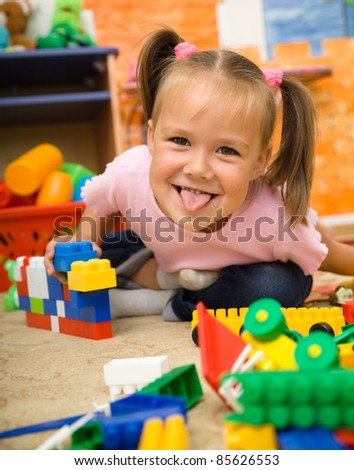 Little girl is showing tongue while playing with building bricks in preschool - stock photo