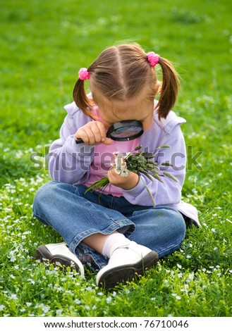 Little girl is sitting on green meadow looking at herbs using magnifier