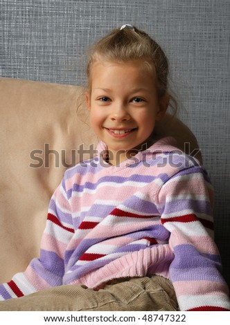 Little girl is sitting on the edge of armchair. She is smiling and looking at camera.