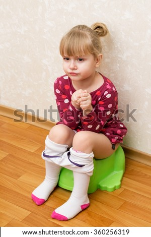 Little girl is sitting on the green children's potty, loose tights - stock photo