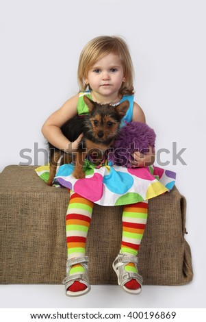 Little girl is sitting with small dog under arm on gray background - stock photo