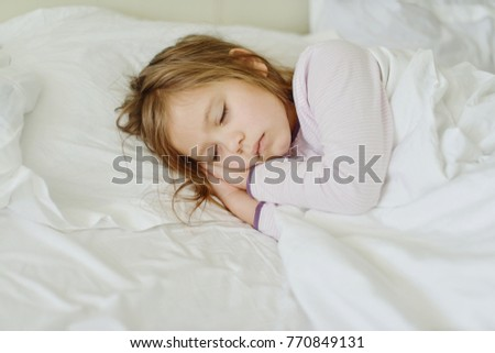 little girl is sleeping in her bed