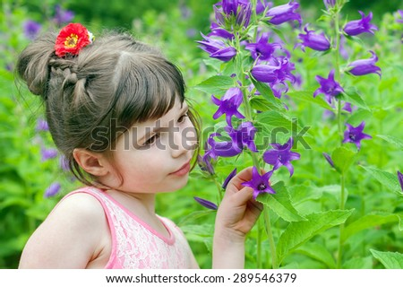 little girl is smelling bluebell - stock photo