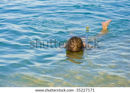 little girl is snorkeling in the sea - stock photo