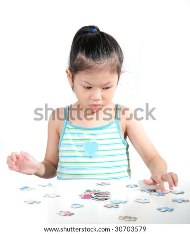 Little girl is solving puzzle on white background - stock photo