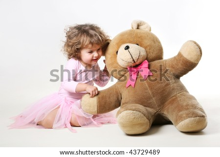 little girl is talking with her teddy - stock photo