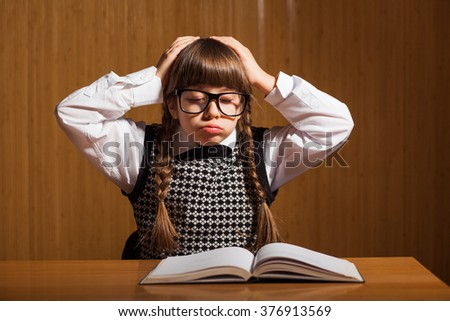 Little girl is tired because she has a lot to learn - stock photo
