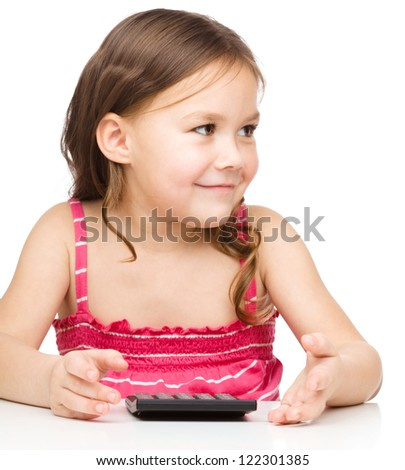 Little girl is using calculator, isolated over white - stock photo