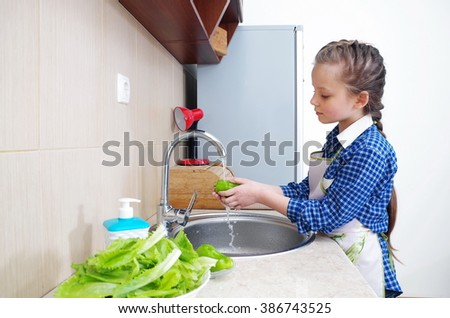 Little girl is washing vegetables for salad closeup