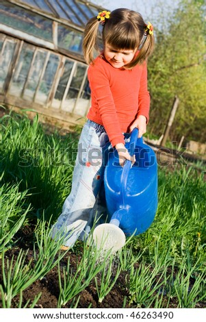 Little girl is watering onion from can on the vegetable garden in spring - stock photo