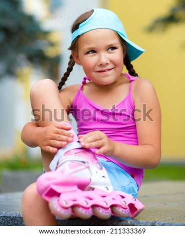 Little girl is wearing roller blades in city park - stock photo