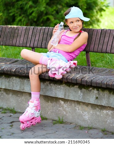Little girl is wearing roller-blades in city park and drinking mineral water - stock photo