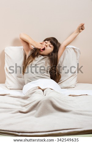 Little girl is yawning and stretching in bed..Good morning world! - stock photo