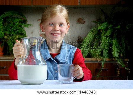 Little girl, jug and mug of milk