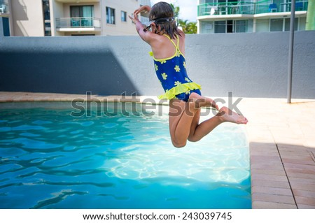 Little girl jumping into swimming pool - stock photo