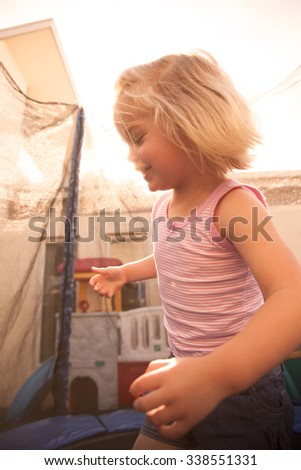 Little girl jumping on a trampoline - stock photo