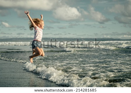 little girl  jumping on the beach at blue sea shore in summer vacation at the day time - stock photo