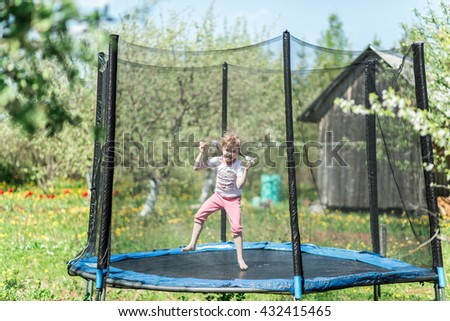 Little girl jumping on the trampoline outside in the summer