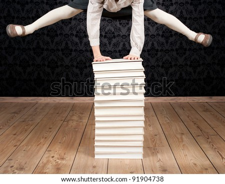little girl jumping through a stack of books - stock photo