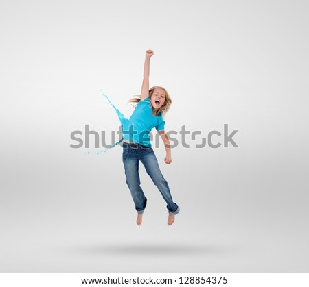 Little girl jumping with clothes turning to paint splashes on grey background - stock photo
