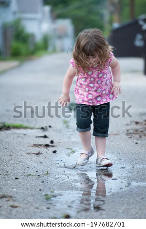 Little girl jumps in a puddle - stock photo