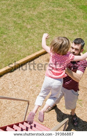 little girl jumps to her father's arms