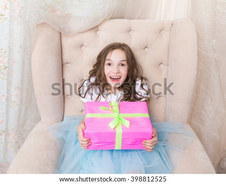 little girl just got her present (gift). Cute little girl hold pink giftbox with ribbon and bow, she sit on chair, happy and surprised face expression - stock photo
