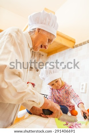 Little girl keeping companion for elderly lady in the kitchen. - stock photo