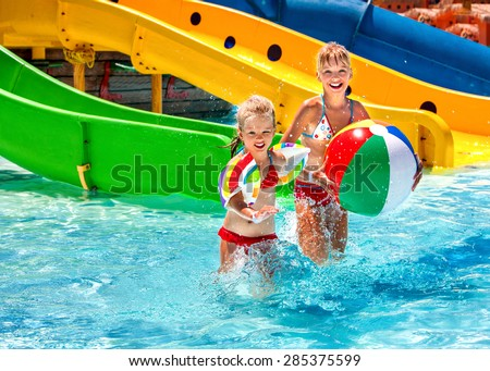Little girl kids playing beach ball in swimming pool.