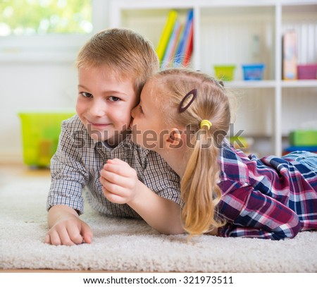 Little girl kiss her happy brother at home - stock photo