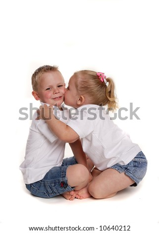 Little girl kissing her brother on the cheek - stock photo