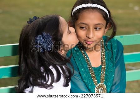little girl kissing her elder sister - stock photo