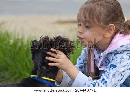 Little girl kissing her pet dog - stock photo