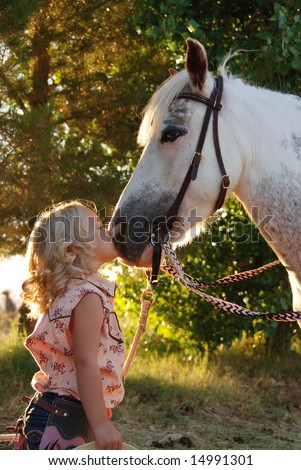 Little girl kissing pony. - stock photo