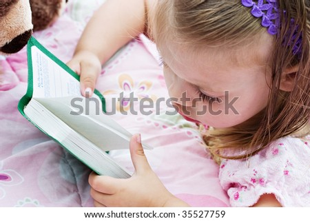 Little girl kneeling by her bed at bedtime and reading a story from her Bible.