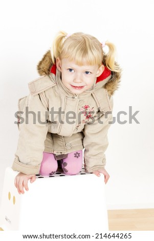little girl kneeling on stool