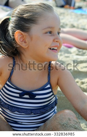 Little girl laugh on the beach. Little girl grin on the beach. little girl playing with the sand. - stock photo