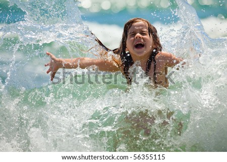 Little girl laughing and crying in the spray of waves at sea on a sunny day - stock photo