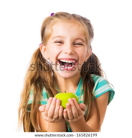 little girl laughing and holding an apple isolated on white background - stock photo