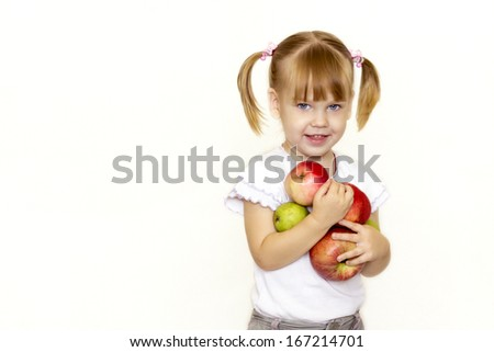 Little girl laughing and trying to hold in the hands of apples and pears .
