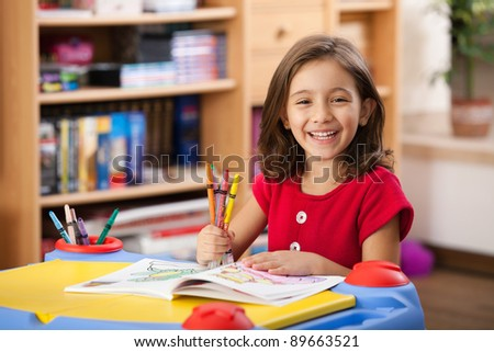 little girl laughing, showing her colorful pencils at her playtable