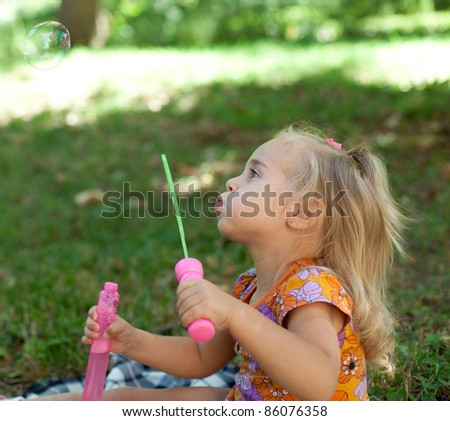 Little girl laughing with bubbles - stock photo