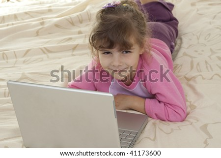 little girl laying in bad playing with a silver laptop and smiling